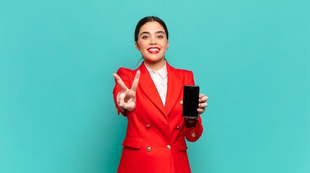 Jonge mooie vrouw die lacht en er vriendelijk uitziet, nummer twee of seconde toont met de hand naar voren, aftellend. slimme telefoon concept