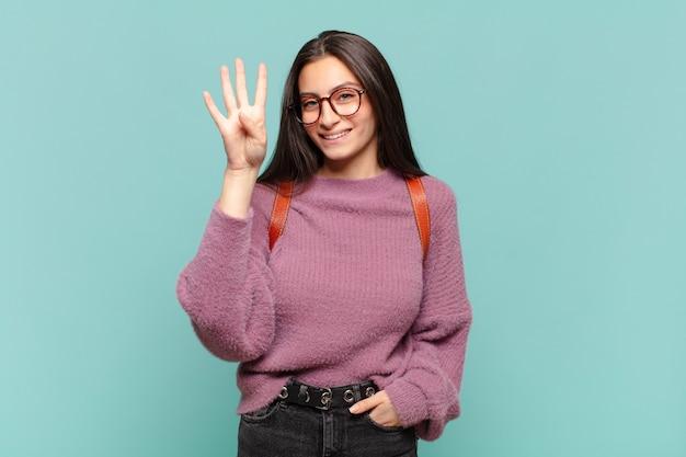 Jonge mooie vrouw die lacht en er vriendelijk uitziet, nummer vier of vierde toont met de hand naar voren, aftellend. studentenconcept