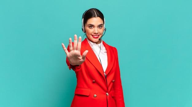 Jonge mooie vrouw die lacht en er vriendelijk uitziet, nummer vijf of vijfde toont met de hand naar voren, aftellend. telemarketeer concept