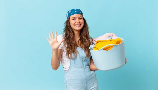 Jonge mooie vrouw die lacht en er vriendelijk uitziet, nummer vijf toont en een wasmand vasthoudt