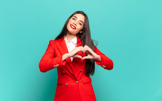 Jonge mooie vrouw die lacht en zich gelukkig, schattig, romantisch en verliefd voelt, en met beide handen hartvorm maakt. bedrijfsconcept