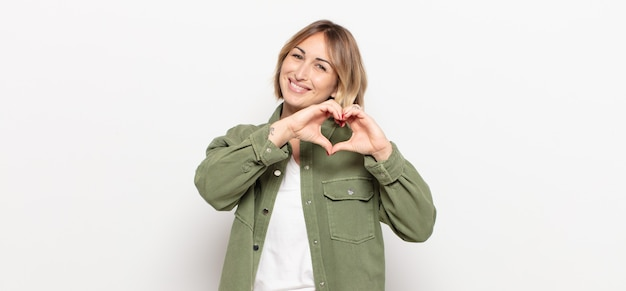 Jonge mooie vrouw die lacht en zich gelukkig, schattig, romantisch en verliefd voelt, hartvorm maakt met beide handen