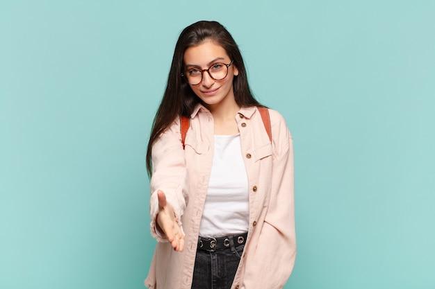 Jonge mooie vrouw die lacht, er gelukkig, zelfverzekerd en vriendelijk uitziet, een handdruk aanbiedt om een deal te sluiten, samen te werken. studentenconcept