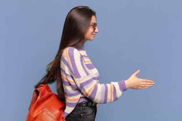 Jonge mooie vrouw die lacht, je groet en een handdruk aanbiedt om een succesvolle deal, samenwerkingsconcept te sluiten. studentenconcept