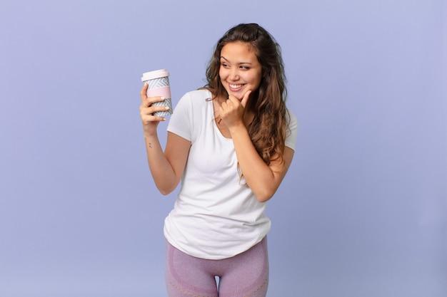 Jonge mooie vrouw die lacht met een gelukkige, zelfverzekerde uitdrukking met de hand op de kin en een kopje koffie vasthoudt