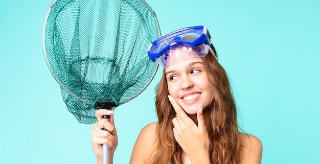 Jonge mooie vrouw die lacht met een gelukkige, zelfverzekerde uitdrukking met de hand op de kin met een bril en een visnet