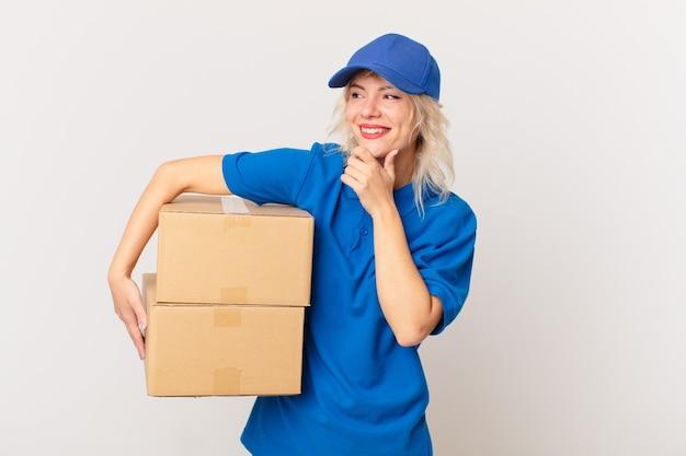 Jonge mooie vrouw die lacht met een gelukkige, zelfverzekerde uitdrukking met de hand op de kin. pakket leveren concept