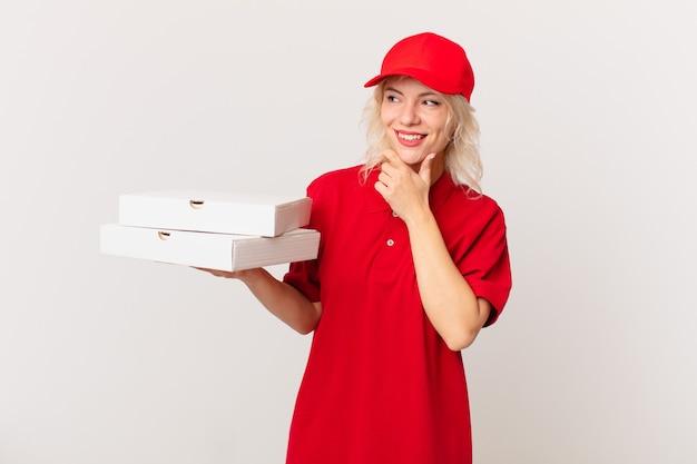 Jonge mooie vrouw die lacht met een gelukkige, zelfverzekerde uitdrukking met de hand op de kin. pizza bezorgconcept