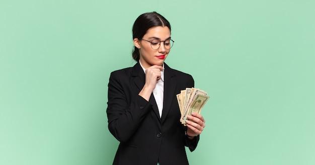 Jonge mooie vrouw die lacht met een gelukkige, zelfverzekerde uitdrukking met de hand op de kin, zich afvragend en opzij kijkend. bedrijfs- en bankbiljettenconcept