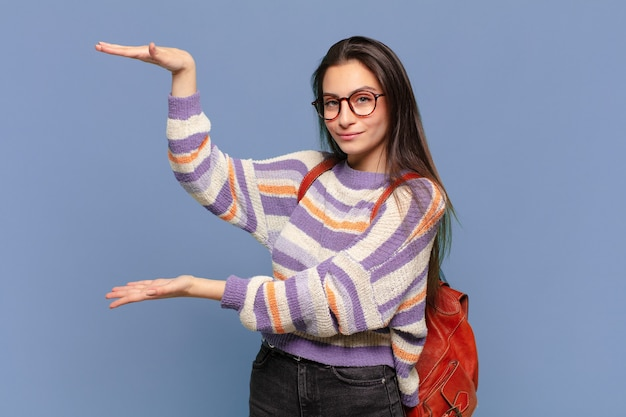 Jonge mooie vrouw die lacht, zich gelukkig, positief en tevreden voelt, object of concept vasthoudt of toont op kopieerruimte. studentenconcept