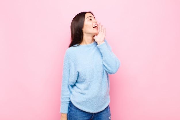 Jonge mooie vrouw die luid en boos schreeuwt om ruimte aan de zijkant te kopiëren, met hand naast mond tegen roze muur