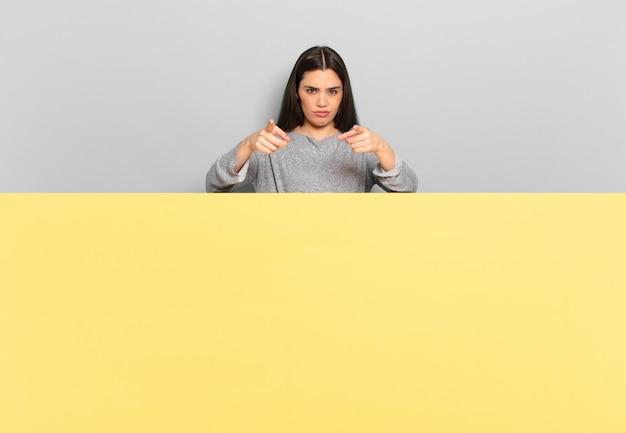 Jonge mooie vrouw die met beide vingers en boze uitdrukking wijst en zegt dat je je plicht moet doen. kopieer ruimte om uw concept te plaatsen