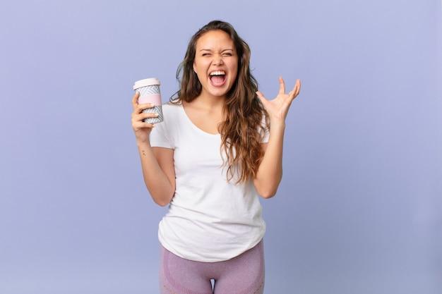 Jonge mooie vrouw die met de handen in de lucht schreeuwt en een kopje koffie vasthoudt