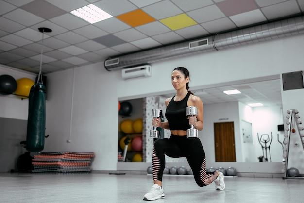 Jonge mooie vrouw die met domoren in de gymnastiek uitwerkt.