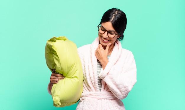 Jonge mooie vrouw die met een gelukkige, zelfverzekerde uitdrukking glimlacht met hand op kin, zich afvraagt en naar de kant kijkt. pyjama's concept