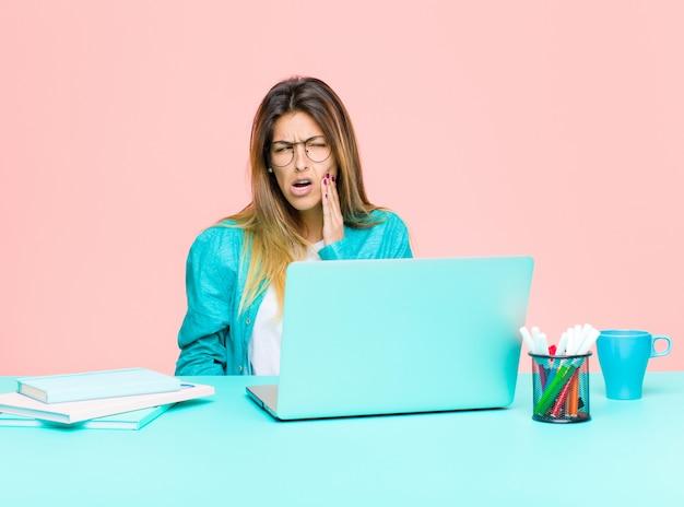 Jonge mooie vrouw die met een laptop met wang werkt en pijnlijke kiespijn lijdt, zich ziek, ellendig en ongelukkig voelt, op zoek naar een tandarts