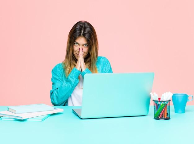 Jonge mooie vrouw die met een laptop werkt, bezorgd, hoopvol en religieus, trouw biddend met palmen ingedrukt, smeken om vergeving