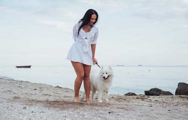 Jonge mooie vrouw die met haar hond op het strand loopt