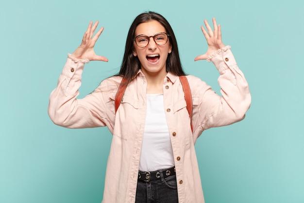 Jonge mooie vrouw die met handen in de lucht gilt, zich woedend, gefrustreerd, gestrest en boos voelt. student concept