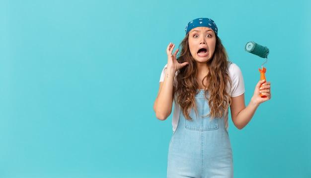 Jonge mooie vrouw die met handen in de lucht schreeuwt en een muur schildert