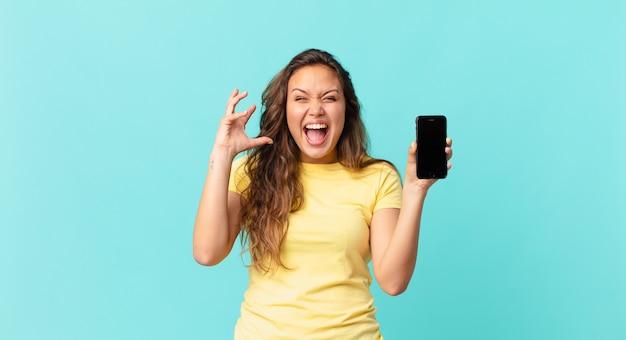 Jonge mooie vrouw die met handen in de lucht schreeuwt en een slimme telefoon vasthoudt