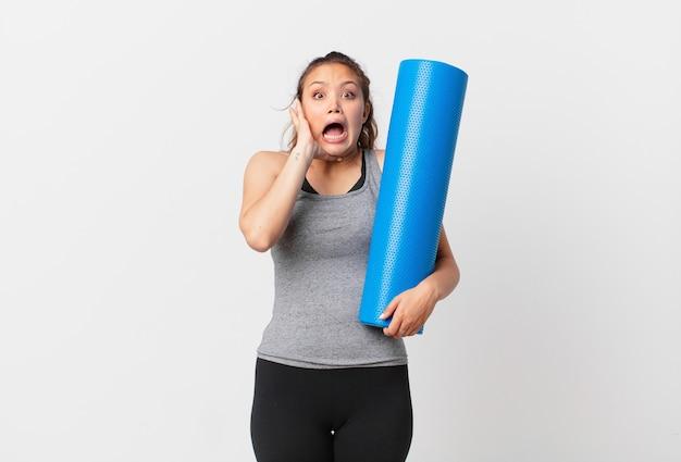 Jonge mooie vrouw die met handen in de lucht schreeuwt en een yogamat vasthoudt