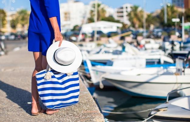 Jonge mooie vrouw die met hoed en zak op dok dichtbij de boot loopt