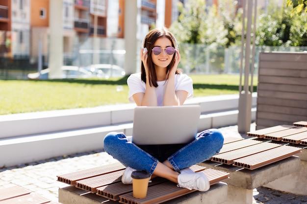 Jonge mooie vrouw die met hoofdtelefoons op bank in het park zitten, die laptop computer met behulp van, die online op draadloos van een netwerk voorzien.
