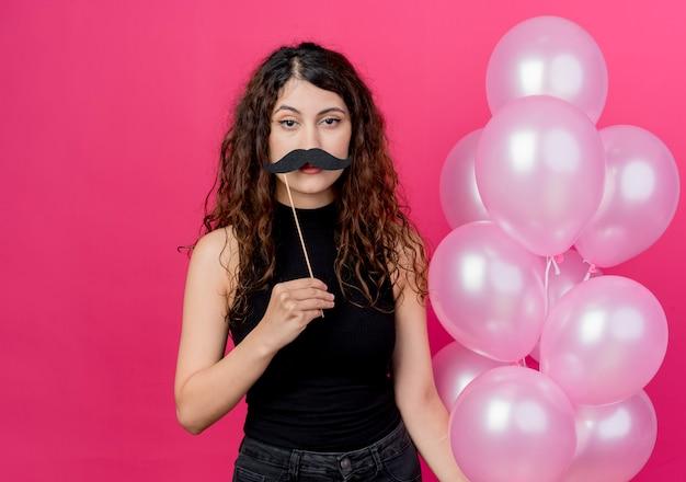 Jonge mooie vrouw die met krullend haar bos van luchtballons en de stok van de snorpartij met ongelukkig gezicht houdt die zich over roze muur bevinden
