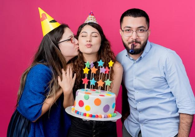 Jonge mooie vrouw die met krullend haar verjaardagstaart met haar de partijconcept van de vriendenverjaardag houdt over roze