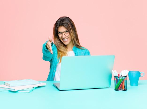 Jonge mooie vrouw die met laptop glimlachen werkt, die gelukkig, zeker en vriendschappelijk kijkt, die een handdruk aanbiedt om een overeenkomst te sluiten