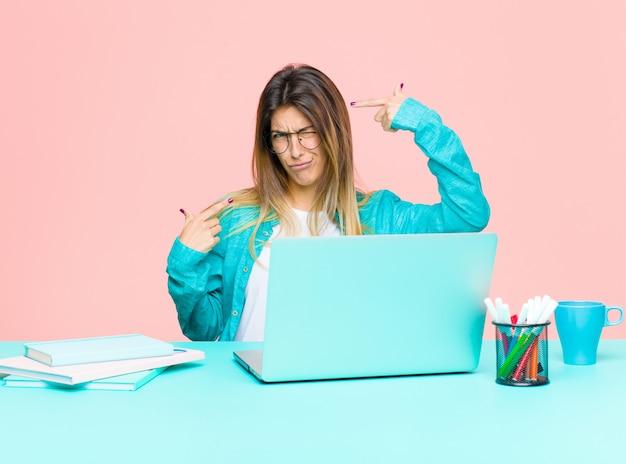 Jonge mooie vrouw die met laptop met een slechte houding werkt die trots en agressief kijkt