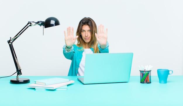 Jonge mooie vrouw die met laptop werkt die ernstig, ongelukkig, boos en ontevreden verbied toegang of zeggend einde met beide open palmen kijkt