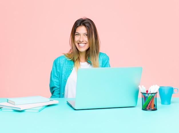Jonge mooie vrouw die met laptop werkt die gelukkig en mal met een brede, leuke, gekke glimlach en wijd open ogen kijkt