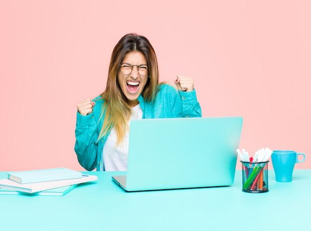 Jonge mooie vrouw die met laptop werkt die gelukkig, positief en succesvol voelen, vierend overwinning, verwezenlijkingen of veel geluk