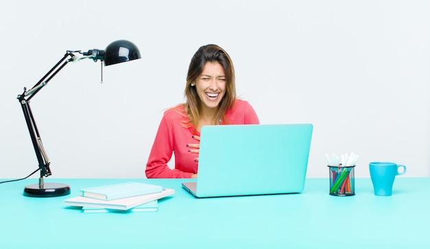Jonge mooie vrouw die met laptop werkt die hard bij één of andere hilarische grap lacht, gelukkig en vrolijk voelt, hebbend pret