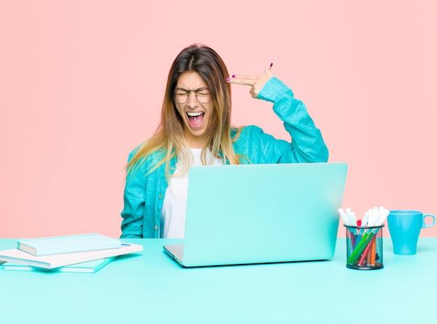Jonge mooie vrouw die met laptop werkt die ongelukkig en beklemtoond, zelfmoordgebaar kijkt dat kanonsteken maakt met hand, die aan hoofd richt