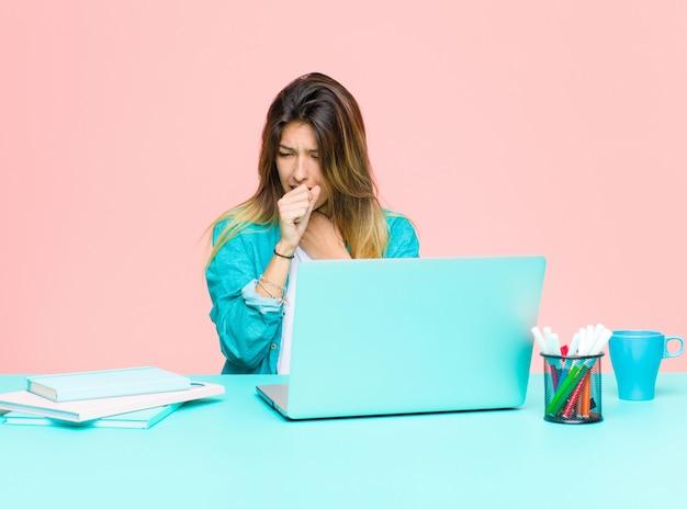 Jonge mooie vrouw die met laptop werkt die ziek met keelpijn en griepsymptomen voelen, hoestend met behandelde mond