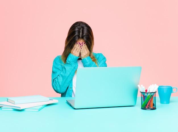 Jonge mooie vrouw die met laptop werkt droevig, gefrustreerd, nerveus en depressief, bedekkend gezicht met beide handen, huilend