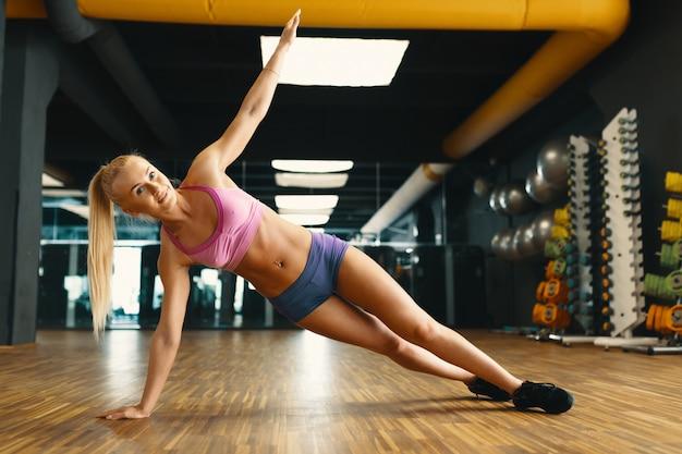 Jonge mooie vrouw die met persoonlijk gewicht in een moderne gymnastiek uitwerkt