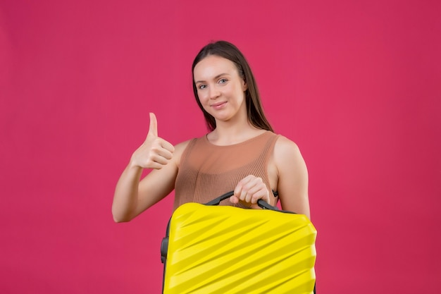 Jonge mooie vrouw die met reiskoffer camera met gelukkig gezicht het glimlachen bekijkt tonen duimen die omhoog zich over roze achtergrond bevinden