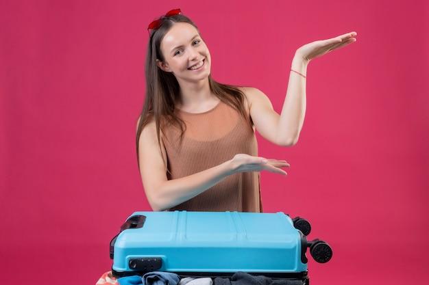 Jonge mooie vrouw die met reiskoffer met wapens van handen voorstellen die vrolijk over roze muur glimlachen