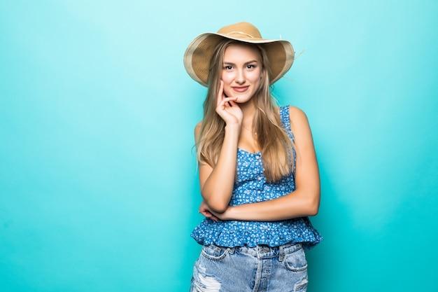 Jonge mooie vrouw die met strohoed en gelukkig op blauwe achtergrond glimlacht