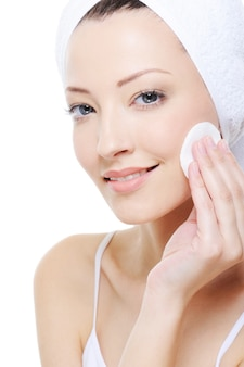 Jonge mooie vrouw die met wattenstaafje haar gezicht schoonmaakt