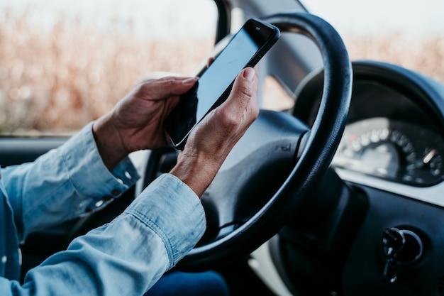 Jonge mooie vrouw die mobiele telefoon in een auto met behulp van. reizen concept