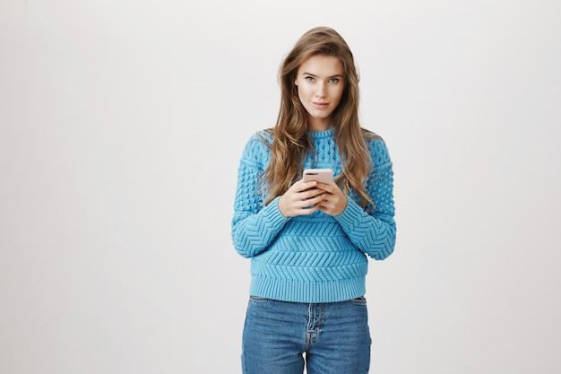 Jonge mooie vrouw die mobiele telefoon met behulp van, kijk camera