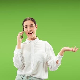 Jonge mooie vrouw die mobiele telefoon met behulp van op groene kleur muur. menselijke gezichtsemoties concept.