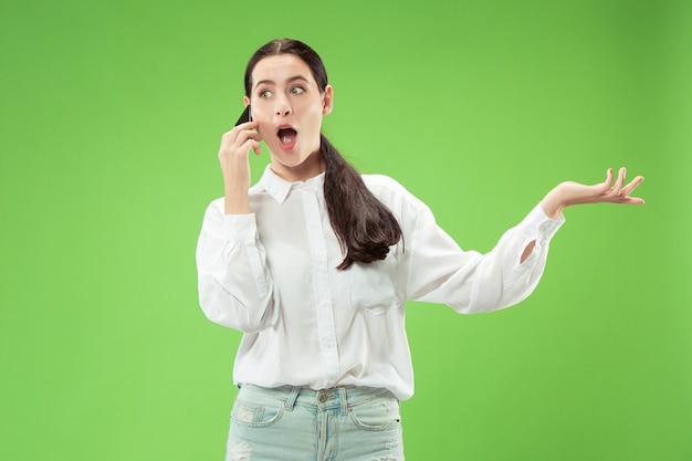 Jonge mooie vrouw die mobiele telefoonstudio op de muur van de groene kleurenstudio met behulp van