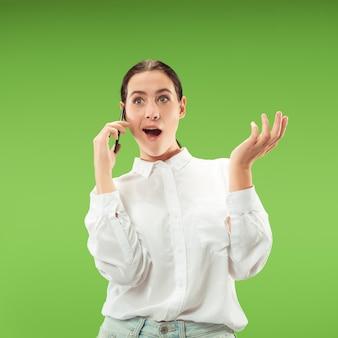 Jonge mooie vrouw die mobiele telefoonstudio op groene kleurenmuur met behulp van