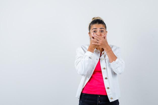 Jonge mooie vrouw die mond bedekt met handen in t-shirt, witte jas en geschokt kijkt. vooraanzicht.
